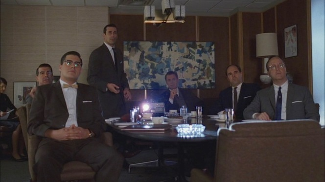 Kodak reps and Sterling Cooper sit back to watch Don's pitch. Harry Crane won't know what hit him.