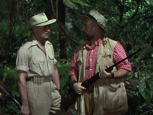 Victor Marswell may have the ammunition on his belt, but his oafish comrade Boltchak (Eric Pohlmann) holds the rifle.