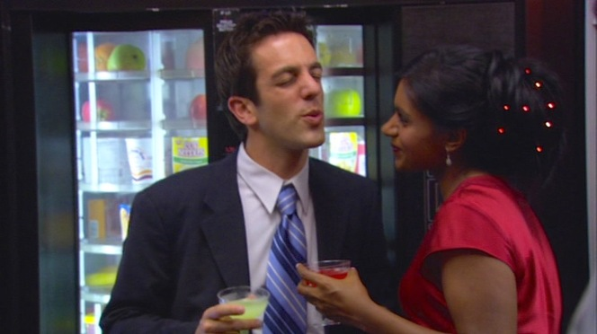 Ryan's cool blues provide a non-festive counter to Kelly Kapoor's holiday red. Yet as much as he tries to resist both Kelly and the office festivities, he soon finds himself with his arms around her singing along to Kevin's karaoke.