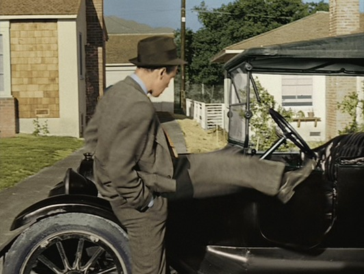 Kicking the door of his jalopy.