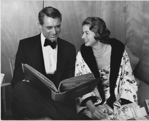 Cary Grant and Ingrid Bergman amuse themselves with newspaper clippings on the set of Indiscreet (1958)
