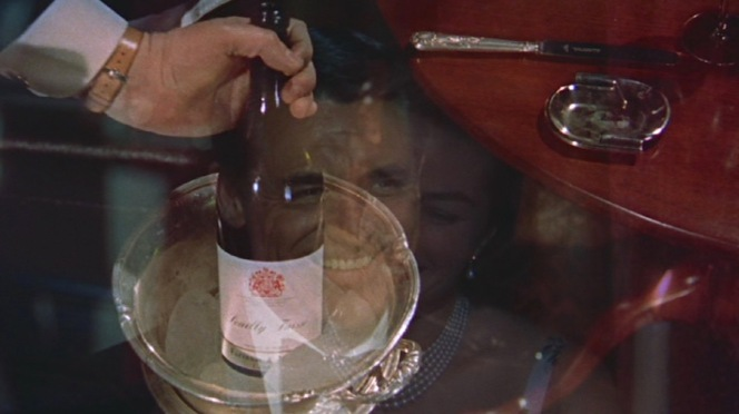 The passage of time is marked during Philip and Anna's date as the waiter removes one bottle of Pouilly-Fuissé to replace it with another. Any oenophiles able to ID the bottle?