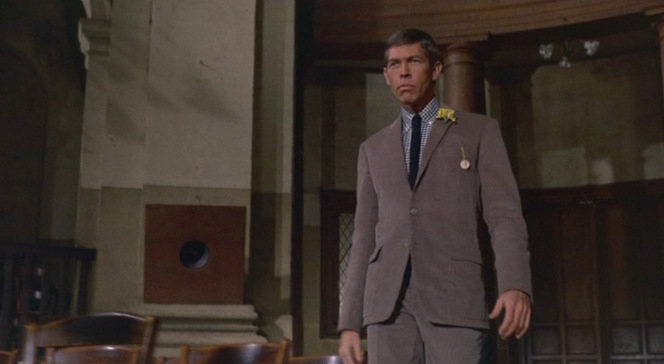 Tex makes his dramatic introduction at Charlie Lampert's funeral, wearing a yellow flower in his lapel.