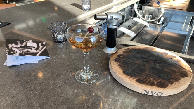 The finished product: a delicious Smoked Manhattan (sans a few heavy sips from yours truly!) next to the well-torched oak plank that helps add the cocktail's distinctive flavor.