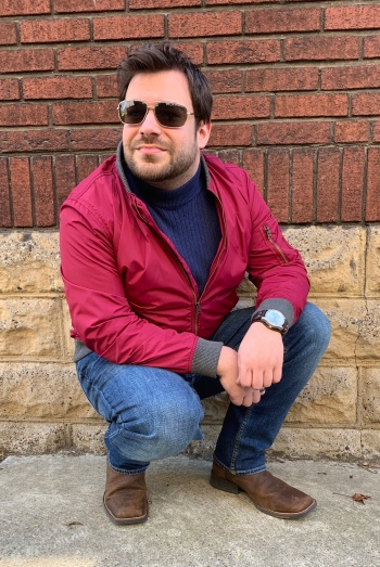 Your humble author in a red nylon Gap jacket with gray knit details, plus navy ribbed cotton Cherokee mock-neck, dark blue Goodfellow & Co. jeans, brown Justin boots, gold-framed Kenneth Cole Reaction sunglasses, and steel UNLISTED by Kenneth Cole watch on bund-inspired strap. Click here to see another view of this outfit with the jacket unzipped to show the Nocona tooled belt.