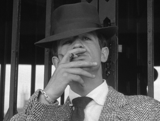 Michel channels Bogie with his hat low, eyes squinted, and cigarette raised.