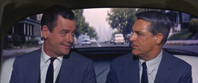 Employee and employer: unified in gray-blue suits and dark ties. Note that Gig Young wears a shirt with a spread collar to complement his longer-shaped head while Cary Grant's point collar complements his wider head.