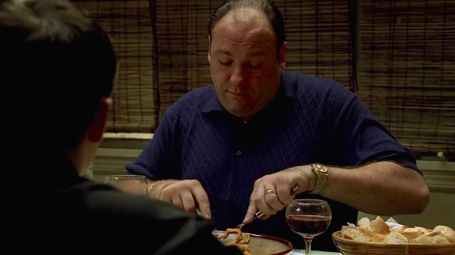 Tony flashes his gold jewelry and accessories during dinner at Meadow's apartment.