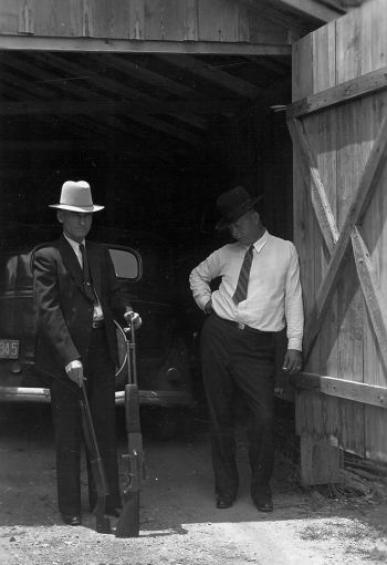The real Maney Gault and Frank Hamer pose with a BAR and Remington Model 11 shotgun found in the Barrow gang's death car, May 1934.