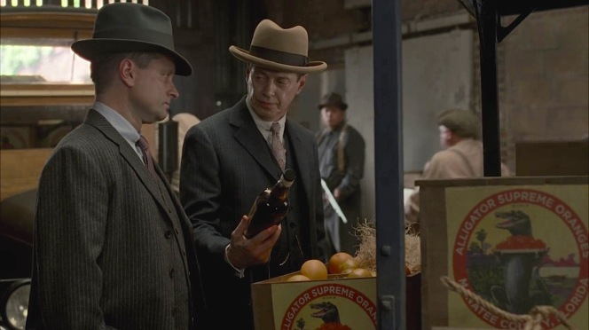 """""""The first bottle. It's good luck,"""" Nucky assures Eli as he hands him a bottle from their latest illegal shipment."""