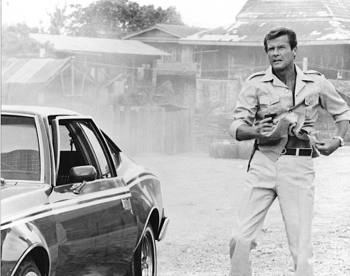 Production photo of Roger Moore as James Bond, drawing his Walther PPK from his trouser waistband in The Man with the Golden Gun. (Source: Thunderballs archive)