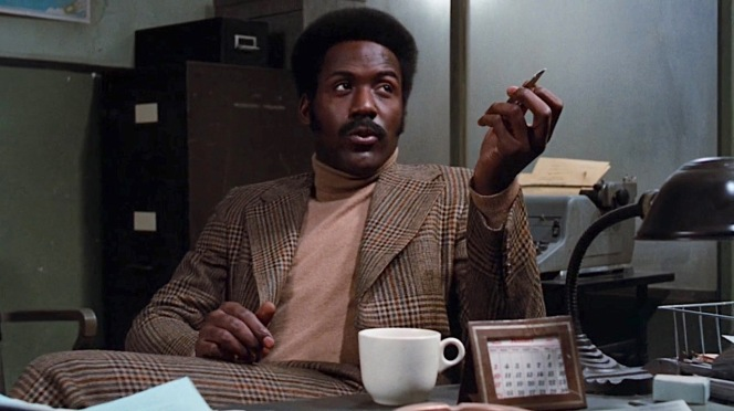 Shaft makes himself at home in Lt. Vic Androzzi's office.