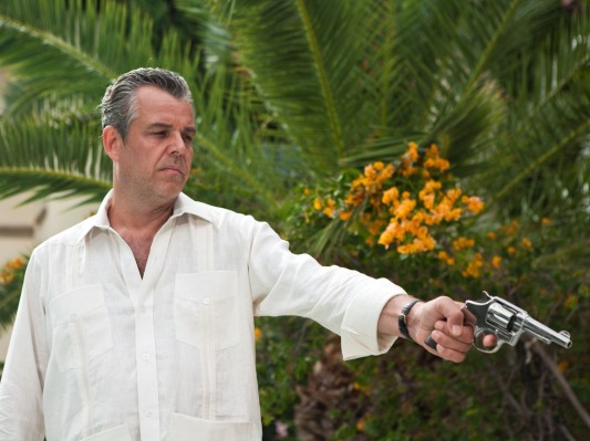 "Production photo of Danny Huston taking aim as Ben Diamond, clad in a white guayabera in ""Feeding Frenzy"" (Episode 1.02)."