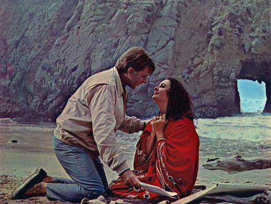 Promotional photo of Richard Burton and Elizabeth Taylor on the beach at Big Sur during the production of The Sandpiper.