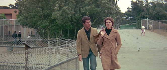 Both Ben and Elaine are coordinated in their tan corduroy jackets and black knit tops. The two may be at odds, but the similar outfits present a subconscious unification to foreshadow to the audience that this fission won't last. In fact, the reunion would result in a romantic reconciliation.