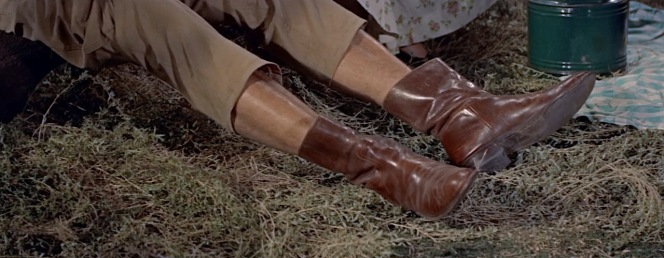 Hal pulls up his pant legs to show off his well-traveled roper boots.