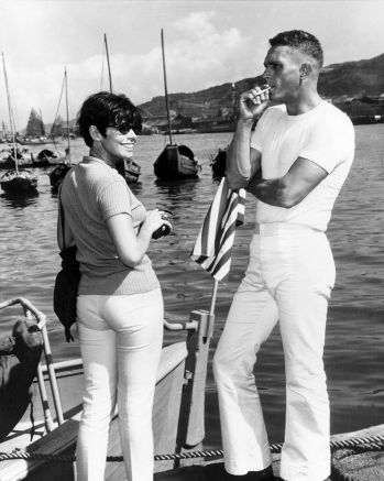 "Steve McQueen enjoys a cigarette while on location in Hong Kong with his then-wife, Neile Adams, circa spring 1966. McQueen is wearing the undershirt and uniform trousers of Holman's white service dress (or ""undress"") uniform."