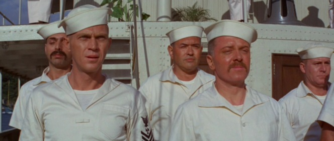 "Holman joins Frenchy and his fellow ship-mates for muster aboard the USS San Pablo, though Holman is dressed in his ""undress whites"" with rank insignia while his fellow sailors wear simplified short-sleeved shirts and shorts."