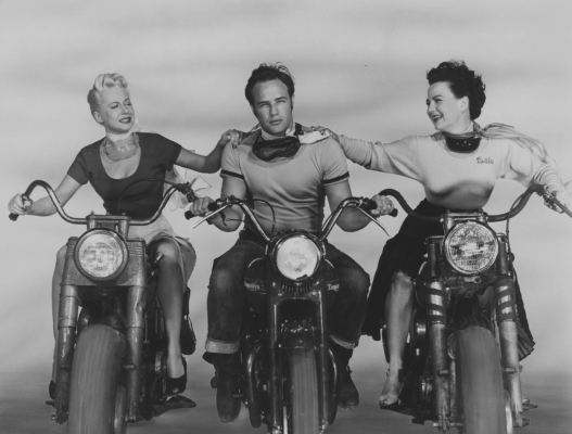 """Promotional photo of Johnny (Marlon Brando), flanked on his Triumph by Mildred (Peggy Mailey) and """"Britches"""" (Yvonne Doughty), both on motorcycles of their own though only Britches was a fellow biker in the film; the blonde Mildred was the beauty shop owner who asked Johnny what he was rebelling against."""