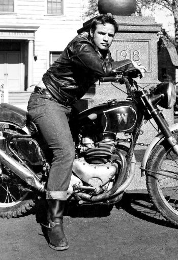 """Costumed in his moto jacket, jeans, and engineer boots, Marlon Brando poses on a Matchless motorcycle used by stunt rider Wally Albright; note the inverted """"M"""" to resemble a """"W""""."""