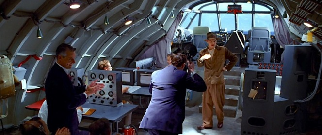 "Hughes in the fuselage of the Hercules before its historic maiden flight, decked out in shades of brown from head to toe, presenting a surprisingly grounded sartorial approach for a man hoping to get his ""Spruce Goose"" into the air. Though Glenn Odekirk is shown in the scene (as Matt Ross' head can be seen here), Odie was not actually on the famous flight as Hughes wanted to remove any doubt that anyone but he was at the controls."