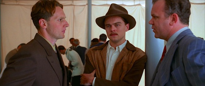 """Everybody works for you, Howard,"" Hughes is assured by Noah Dietrich (John C. Reilly), here conferring with chief engineer Glenn Odekirk (Matt Ross) before the two quickly usher an increasingly panicking Hughes out of public view."