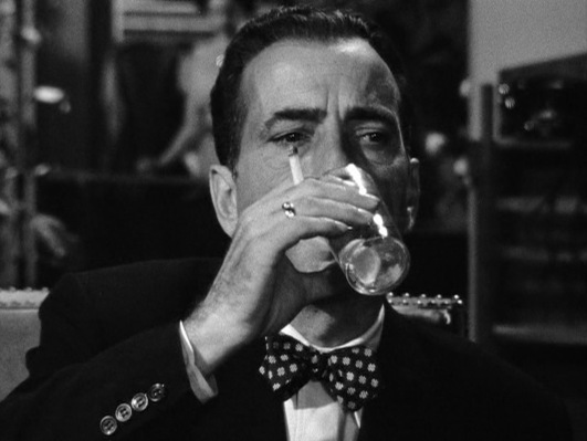 Classic Bogie: gold shiner gleaming from the same hand that simultaneously holds his drink and his cigarette. Never before or since has a polka-dot bow tie looked so badass.