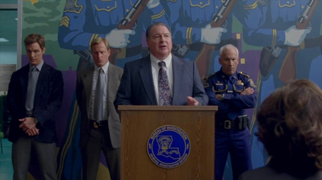 Cohle joins Hart behind Quesada as the LSP conducts their briefing to the press.