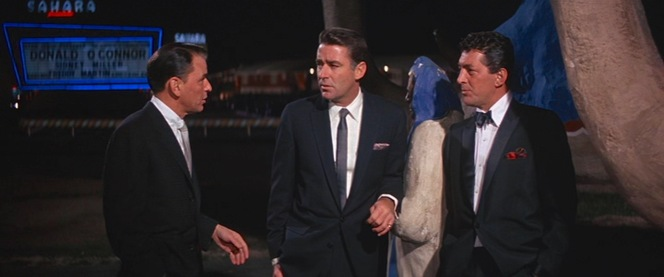 Frank Sinatra and Peter Lawford sport dark lounge suits edged out in formality only by the dinner suit, though Dean Martin dresses down his famous tux by wearing it with one of his usual button-down collar shirts.