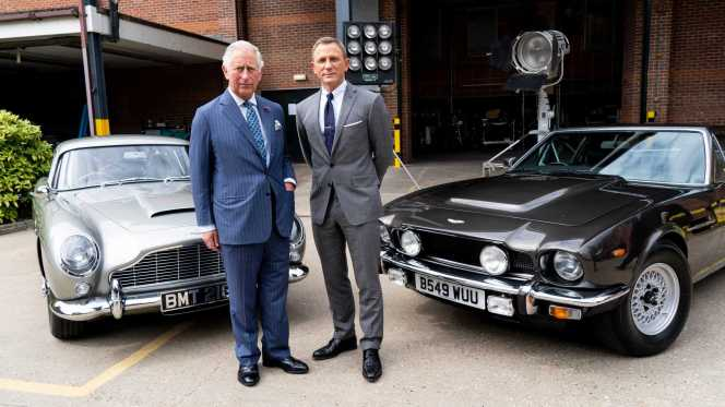 Prince Charles and Daniel Craig on the No Time to Die set earlier in 2019, flanked by the 1964 Aston Martin DB5 and the 1980s Aston Martin V8.
