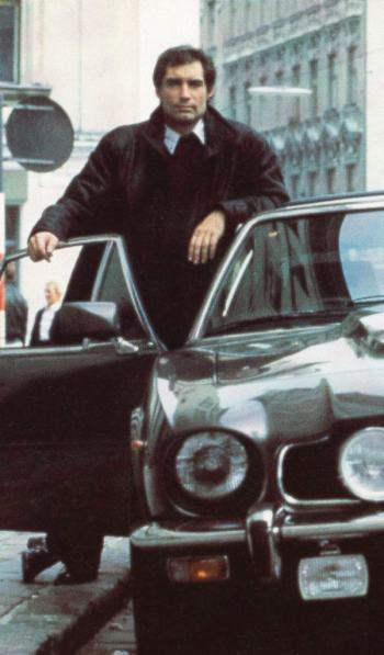 Timothy Dalton poses with an Aston Martin V8 as James Bond in The Living Daylights (1987)