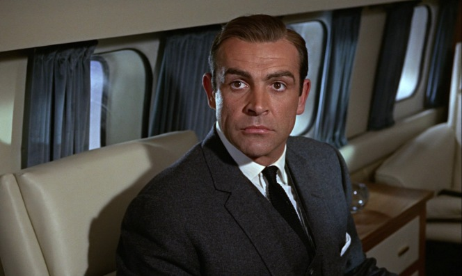 Bond regards the unexpected arrival of his co-passenger.