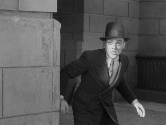 A volley of live machine gun fire narrowly misses killing Tom... and killing James Cagney.