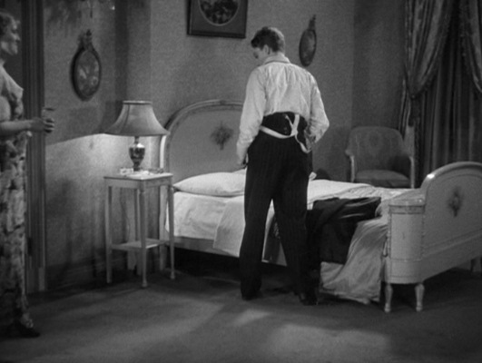 His suspenders down by his sides, Tom gets ready to stumble into bed.