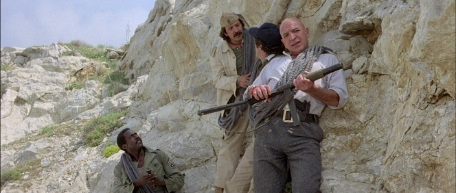Zeno tucks his Walther into his trousers and carries his Sten gun as he leads Sgt. Nat Judson (Richard Roundtree), Bruno Rotelli (Sonny Bono), and Charlie Dane (Elliott Gould) into combat.