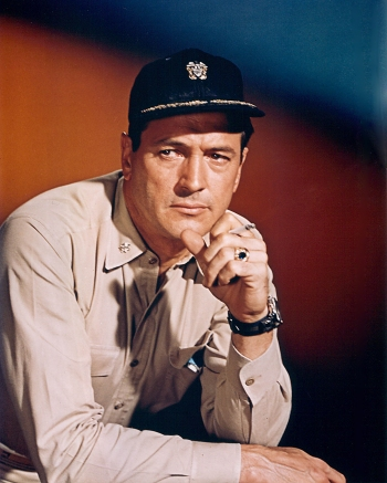 """Rock Hudson in Commander Ferraday's khaki working uniform, complete with silver O-5 oak leaf collar devices and navy ballcap with """"scrambled eggs"""" on the brim."""