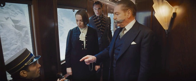 Poirot confronts conductor Pierre Michel (Marwan Kenzari) with a conductor's uniform—missing a button—found in his compartment, consistent with the description Hildegarde Schmidt (Olivia Colman) provided of a suspicious man aboard the train around the time of the murder.
