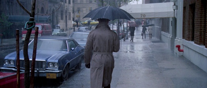 The first we see of Joubert, he is walking away from the camera on a rainy morning in Manhattan, adequately protected with an umbrella and trench coat.