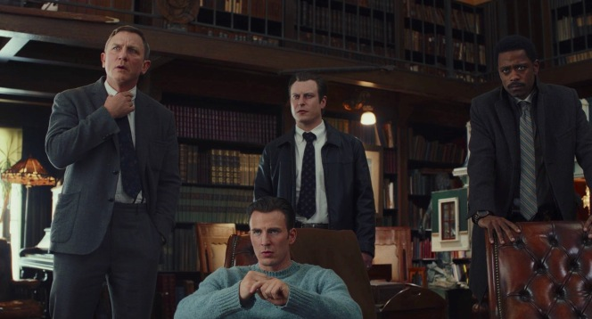 The three investigators—Blanc, Trooper Wagner (Noah Segan), and Lieutenant Elliot (Lakeith Stanfield)—stand around a seated Ransom Drysdale (Chris Evans).