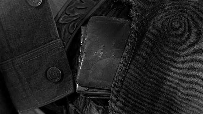 """One of the first shots we get of Dove Linkhorn's jacket clearly establishes it as a Lee Storm Rider as the riveted buttons are branded """"Lee RIDERS"""". While his wallet was undoubtedly meant to be the focus of this shot, the style blogger in me couldn't help but to notice the branded buttons first!"""