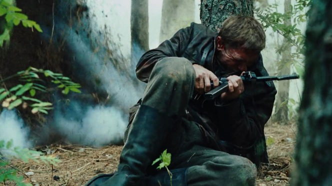 MP40 in hand, Tuvia takes cover behind a tree while battling the Germans.