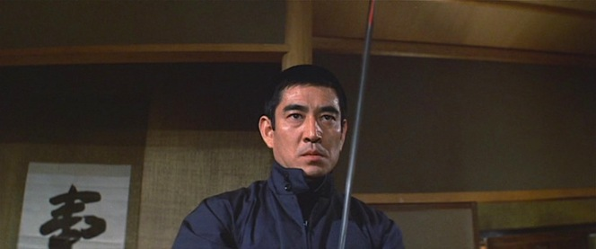 Baracuta jacket zipped high and blade bloodied at the tip, Ken prepares for combat.