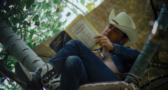 Relaxing in cowboy hat and boots in a pose reminiscent of his hero James Dean on the set of Giant, Kit casts a furtive glance around while poring through a National Geographic... as if reading a magazine was the only thing he had to feel guilty about.