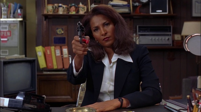 """Jackie practices drawing the Detective Special to ensure that she'll have an advantage over Ordell, if needed. As Amy the saleswoman had predicted, Jackie Brown is indisputably """"the badass in the room."""""""
