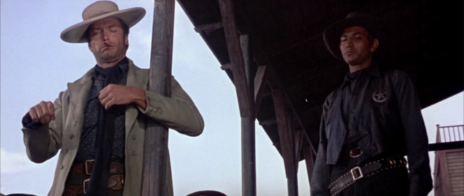 Blondie regards his latest bounty, a seething Tuco, before accepting $2,000 for bringing the irate bandit to be hanged.