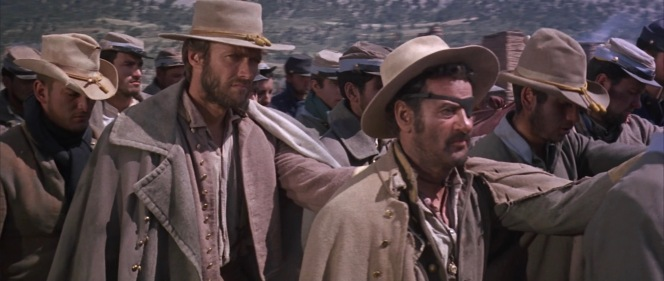 """Hardly the pride of the Confederacy, Blondie and Tuco's latest gambit lands them among bona fide rebels in a Union prison camp, ruthlessly run by Corporal Wallace (Mario Brega) and the newly ordained Sergeant """"Angel Eyes"""" (Lee Van Cleef)."""