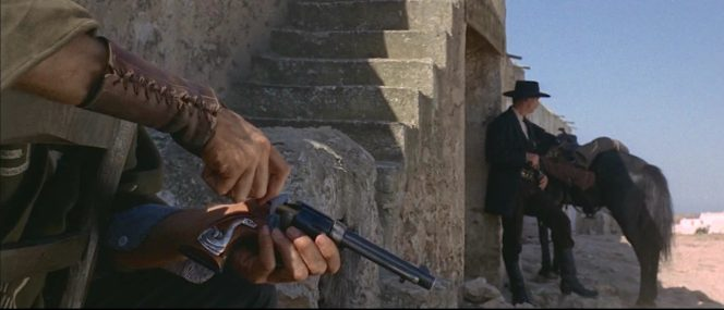 """The Man with No Name loads his snake-gripped Single Action Army in For a Few Dollars More, the only installment of the """"Dollars trilogy"""" where Eastwood also wore this long brown leather lace-up shooting cuff on his right forearm."""