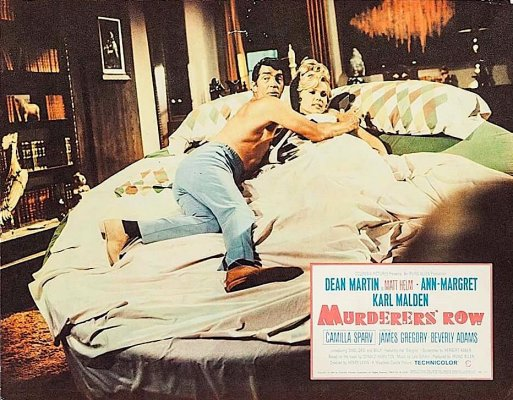 This promotional lobby card for Murderers' Row depicts Matt and Miss January in flagrante delicto just before she orchestrates his explosive assassination.