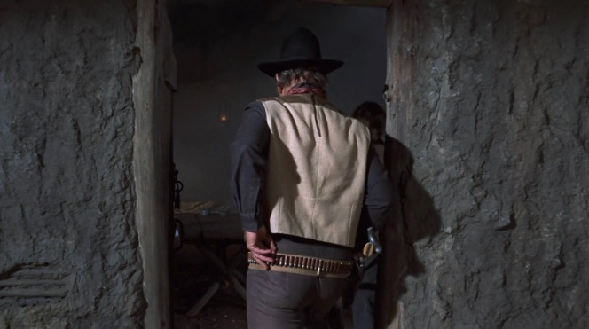 Rooster charges into the hideout where horse thieves Quincy (Jeremy Slate) and Moon (Dennis Hopper) have taken refuge.