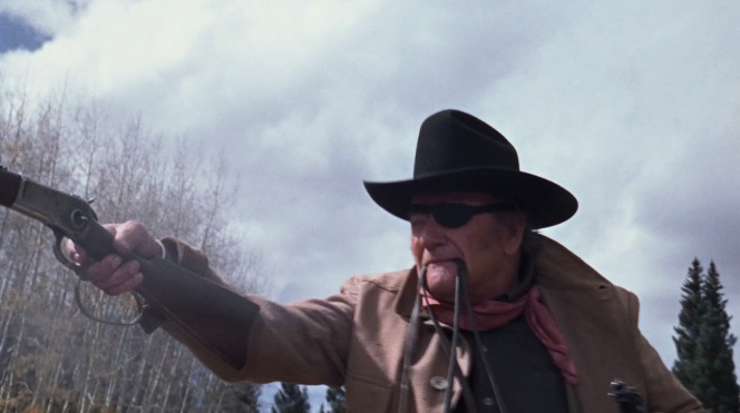 Rooster fires his Winchester one-handed.
